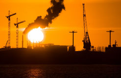 Industry silhouettes, pollution and big sun Stock Images