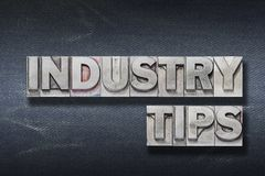 Industry tips den. Industry tips phrase made from metallic letterpress on dark jeans background stock image