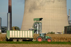 Industry and Tractor. Heavy Oil Industry with a field of corn and a tractor stock photo