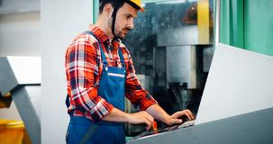 Industry Worker entering data in CNC machine at factory Royalty Free Stock Image