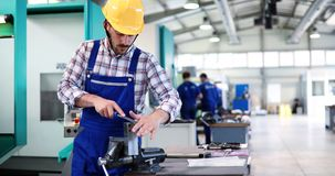 Industry Worker entering data in CNC machine at factory Royalty Free Stock Images