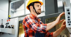 Industry Worker entering data in CNC machine at factory Royalty Free Stock Photography