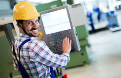 Industry Worker entering data in CNC machine at factory Stock Photography