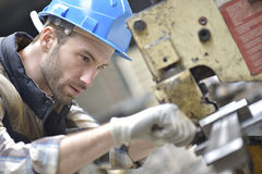 Industry worker working on machine in factory Stock Image