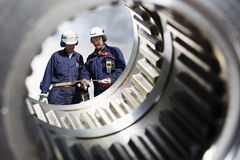 Industry workers and gears shaft. Two industry workers, engineers, seen through a giant gears shaft, natural colors Stock Image