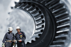 Industry workers and large gears Royalty Free Stock Photos