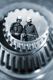 Industry workers and machinery. Two industry workers, engineers, seen through the inside of giant gear wheels, blue toning concept Royalty Free Stock Photography