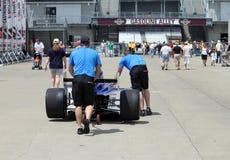 Indy 500 membri della squadra della corsa che spingono una macchina da corsa verso il vicolo della benzina Fotografie Stock
