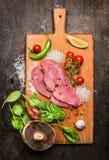 Indyczy stek na tnącej desce z pieczarkami, zielonych pieprzy pomidorami i cytryna czosnkiem na drewnianego nieociosanego tła odg obrazy stock