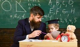 Indywidualny uczy kogoś pojęcie Nauczyciel i uczeń w mortarboard, chalkboard na tle Dzieciak studiuje pojedynczo z obrazy stock