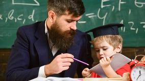 Indywidualny uczy kogoś pojęcie Ojcuje z brodą, nauczyciel uczy syna, chłopiec Dzieciak studiuje pojedynczo z nauczycielem obraz royalty free