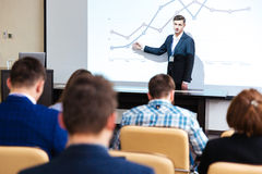Inelligent speaker standing and lecturing at business conference. In boardroom stock photo