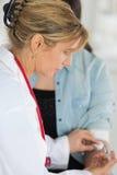 Inenting - de vrouwelijke arts met spuit geeft injectie Royalty-vrije Stock Afbeelding