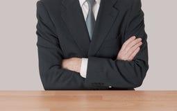 Inerzia - uomo allo scrittorio con le braccia attraversate Immagini Stock