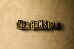INEXPENSIVE - close-up of grungy vintage typeset word on metal backdrop Royalty Free Stock Photography
