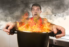 Inexperienced home cook with apron holding pot burning in flames with stress panic face expression Stock Photography