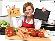 Inexperienced home cook woman in red apron screaming desperate and frustrated at domestic kitchen in stress Stock Photos