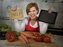 Inexperienced home cook woman in red apron screaming desperate and frustrated at domestic kitchen in stress Stock Images