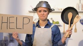 Inexperienced lady with colander on head holding kitchen utilities and help sign stock video