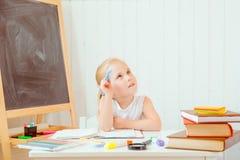 Infância e de volta ao conceito da escola Menina com expressão pensativa da cara fotos de stock royalty free