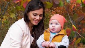 A infância e a maternidade feliz, o mum e a criança no outono estacionam ter o close-up do divertimento fora no fundo de árvores  filme