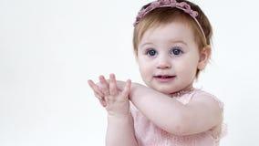 Infância feliz, criança fêmea bonito com os olhos grandes azuis que aplaudem as mãos no fundo branco filme