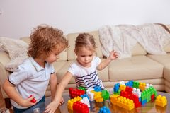 Infância feliz - irmão e irmã que jogam com brinquedos e que têm o divertimento junto foto de stock