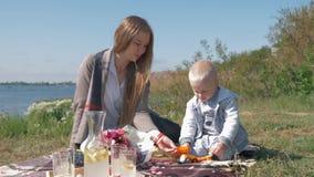 A infância feliz, mamã nova é brinquedos jogados com o bebê bonito durante o piquenique da família na natureza perto do rio no fi filme