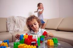Infância feliz - menino bonito que joga com brinquedos em casa foto de stock royalty free