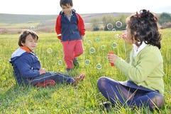Infância feliz no prado verde Fotos de Stock Royalty Free