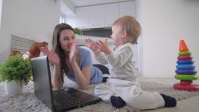 Infância moderna, menino feliz da criança com as teclas novas laptop da mãe e mãos do aplauso que encontram-se no assoalho video estoque