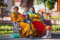Infödd infödd dam och barn i traditionell färgrik klänning i trädgården, Mexico, Amerika arkivfoto