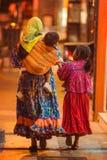 Infödd fattig infödd dam och barn i traditionell färgrik klänning i staden på natten, Mexico, Amerika arkivbilder