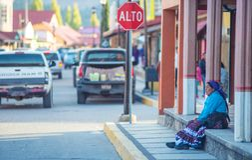 Infödd infödd gammal dam i traditionell klänning i färgrik stadsgata, i fiskkorg, Mexico, Amerika royaltyfri fotografi