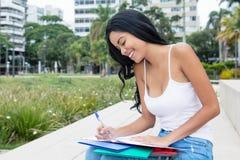 Infödd latin - amerikansk kvinnlig student som utomhus lär på universitetsområde arkivbilder