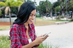 Infödd latin - amerikanskt kvinnahälerikort på telefonen arkivbilder