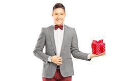 Infall klädd ung man som rymmer en gåva royaltyfri bild