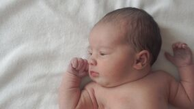 Infancy, childhood, development, medicine and health concept - close-up face of newborn naked calm awake baby grimaces
