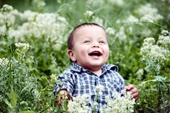 Infant. Plays in tall grass, and smiles