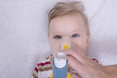 Infant with asthma inhalator. Infant using an asthma inhalator Royalty Free Stock Image