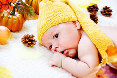 Infant  among autumnal leaves and pumpkins Stock Photo