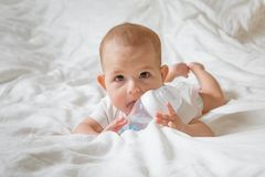 Infant baby with big brown eyes lying on the white bed and licks special bottle of water with nipple. Tries to gnaw her. teething. Child childhood caucasian royalty free stock images