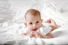 Infant baby with big brown eyes lying on the white bed and licks special bottle of water with nipple. Tries to gnaw her. teething. Child childhood caucasian royalty free stock photo