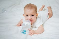 Infant baby with big brown eyes lying on the white bed with special bottle of water with nipple. Tries to gnaw her. teething. Child childhood caucasian cute stock photography