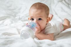 Infant baby with big brown eyes lying on the white bed with special bottle of water with nipple. Tries to gnaw her. teething.  royalty free stock image