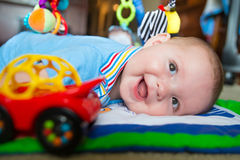 Infant baby boy playing on activity mat Royalty Free Stock Image