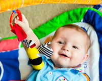 Infant baby boy playing on activity mat Royalty Free Stock Photo