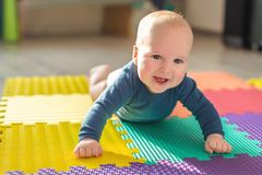 Infant baby boy playing on colorful soft mat. Little child making first crawling steps on floor. Top view from above stock image