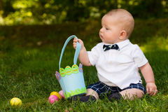 Infant baby boy playing with Easter eggs and basket. Cute infant baby boy playing with Easter eggs and basket Stock Photography