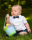 Infant baby boy playing with Easter eggs and basket Stock Photos